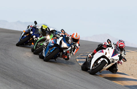 Motorcycle racers making a corner all wearing motorbike helmets