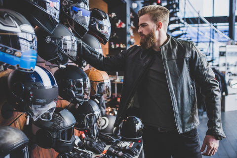 Man looking at the rack of motorbike helmets in the store