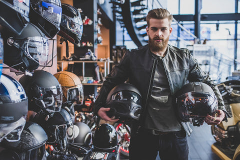 Man holding a motorbike helmet in a store