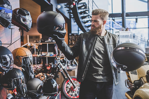 Man comparing a cheap motorbike helmet to an expensive one