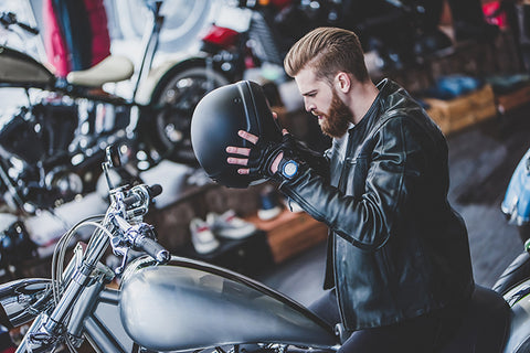Man looking at a cheap motorbike helmet in a motorcycle shop