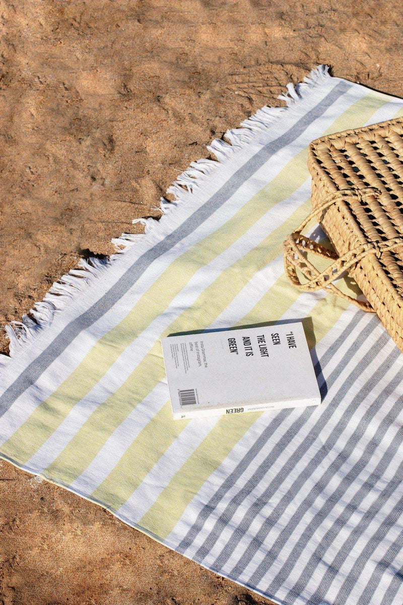 Luzia Peshtemal Beach and Pool Towel in Yellow and Grey on the Beach with Book