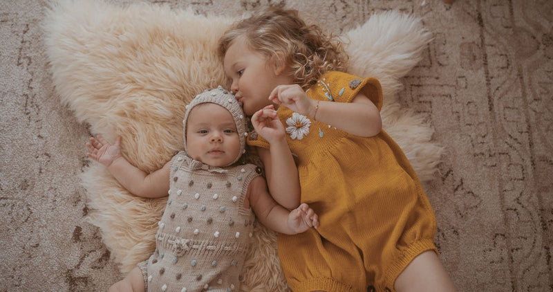 Little girls in Shirley Bredal hand knitted rompers