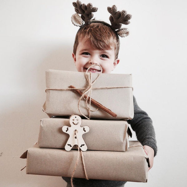 Little boy holding gifts and shirley bredal antlers on a head