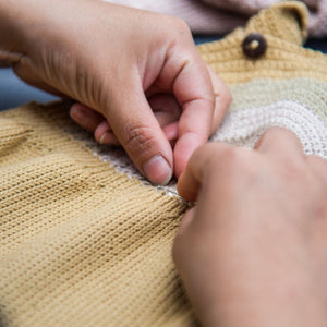 Process of hand-knitting baby romper in our Kathmandu studio