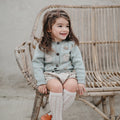 Little cute girl sitting in chair wearing hand knitted cardigan in duck blue which has beautifully hand embroidered floral design in the front part, it suits perfectly with her outfit