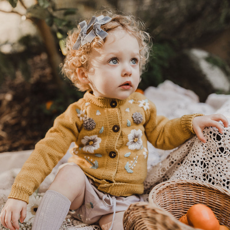 Cute baby girl wearing hand knitted mustard cardigan with beautifully embroidered floras on it, mainly in the front part. The cardigan fits perfectly with her sweet outfits