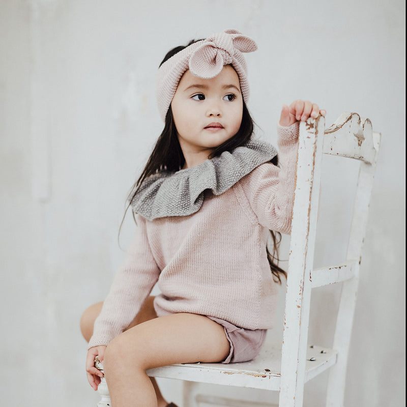 baby girl sitting in a chair wearing hand knitted dusty pink sweater