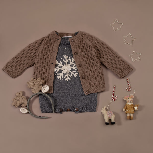 flat lay picture of hand knitted snowflake romper along withh smock cardigan nutty brown