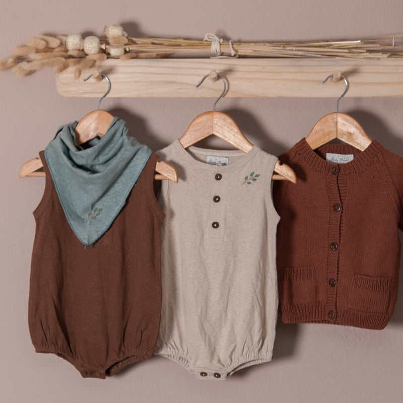 baby romper cognac and oats in hemp cotton with scarf hanged in coat rack along with hand knitted cardigan