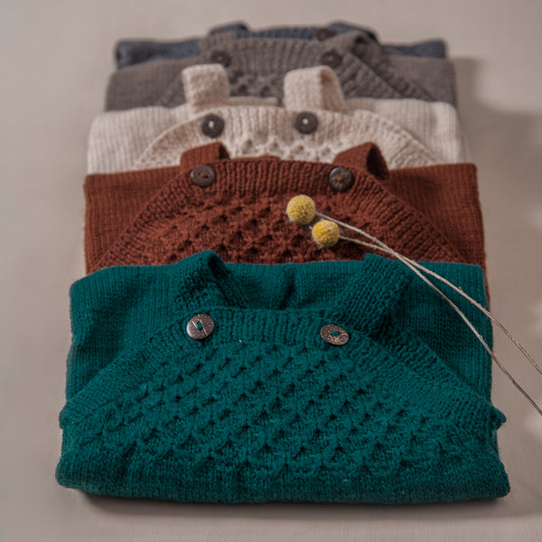 flat lay picture of hand knitted smock jumpsuit in different colours