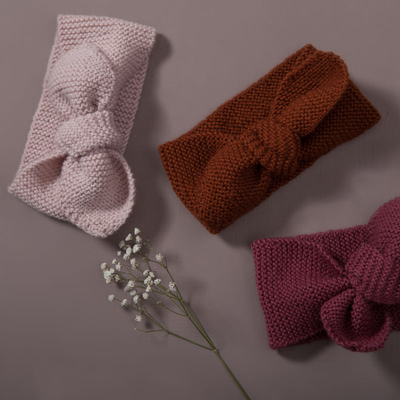 Flat lay picture of hand knitted baby hair band, three piece in three different color : dusty pink, rust  and deep berry