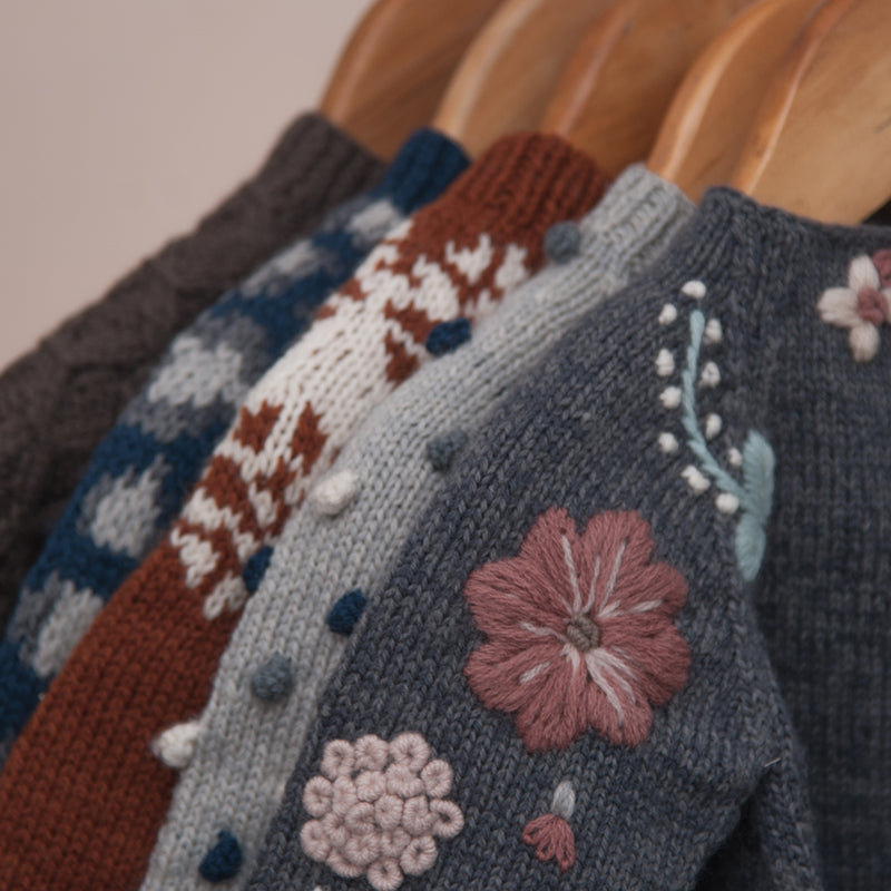Detail picture of different hand knitted sweater along with flora sweater in front