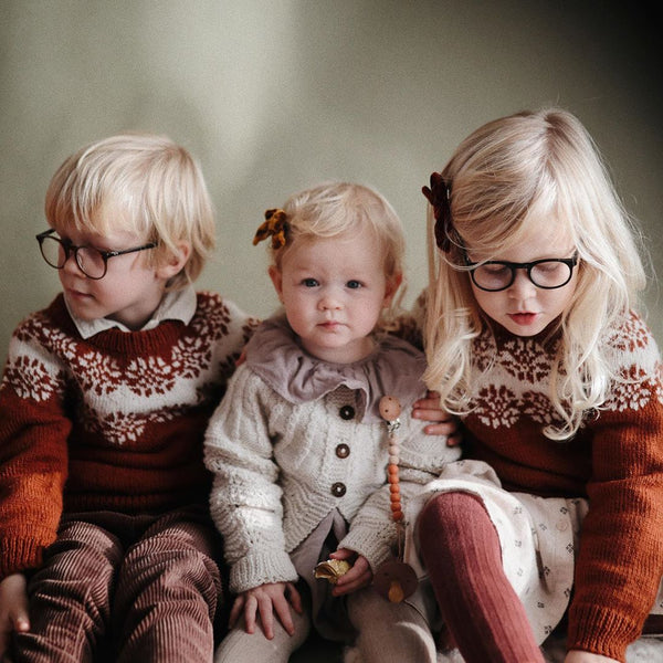 three cute siblingspictures and two of them wearing hand knitted sweater with frost design on it