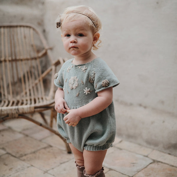 baby girl wearing hand knitted romper with floral embroidery on the front chest  and sleeve part, she looks so adorable on this outfit