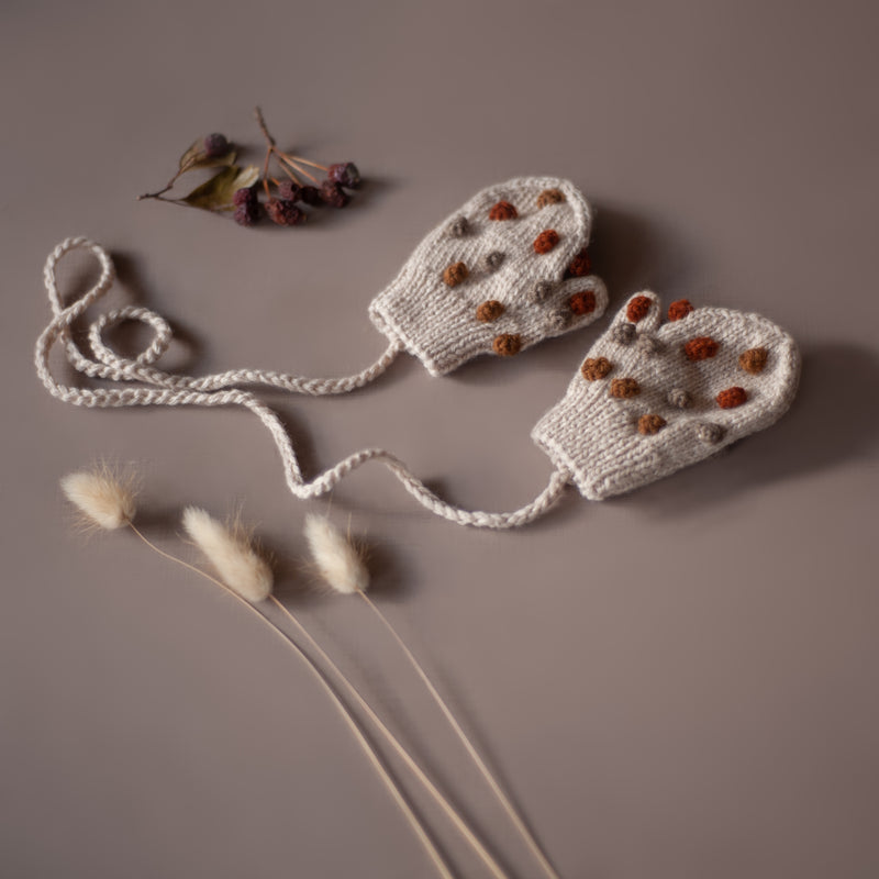 flatlay of hand knitted mittens in bubble style