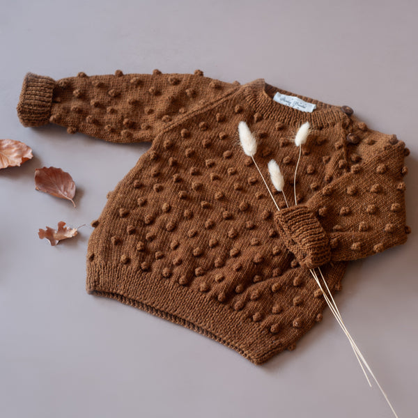 Flat lay picture of hand knitted sweater on bubble style, caramel