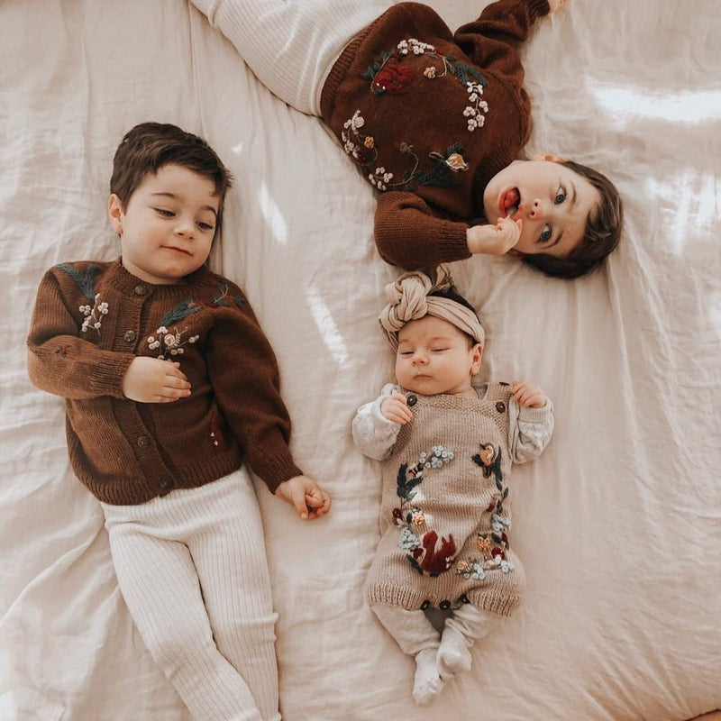 baby boys wearing woodland cardigan caramel, other wearing woodland sweater caramel and little baby girl wearing woodland romper oats