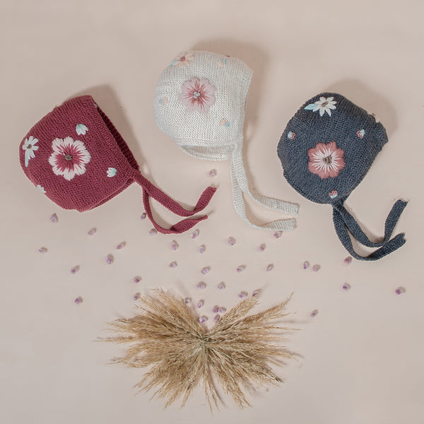 flat lay picture of 3 different coloured piece of hand knitted bonnet with string ties on it and with floral embroidery on both sides of the bonnet