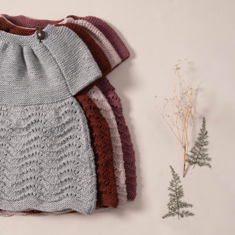 flat lay picture if hand knitted dress in ligt grey,rust,dusty pink and deep berry