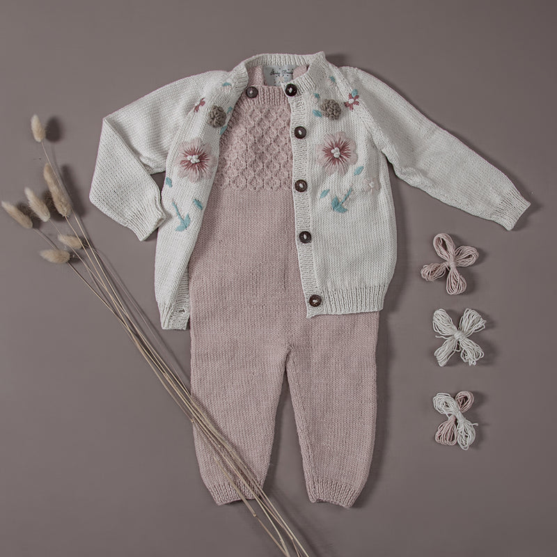Flat lay picture of hand knitted baby jumpsuit dusty pink and hand knitted  cardigan with hand made floral embroidery on it.