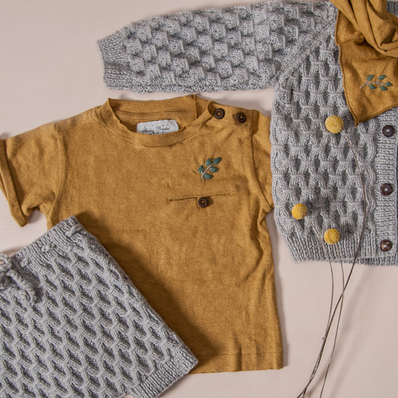 Flat lay picture of baby t-shirt in hemp cotton fabric masala along with hand knitted cardigan and hand knitted shorts