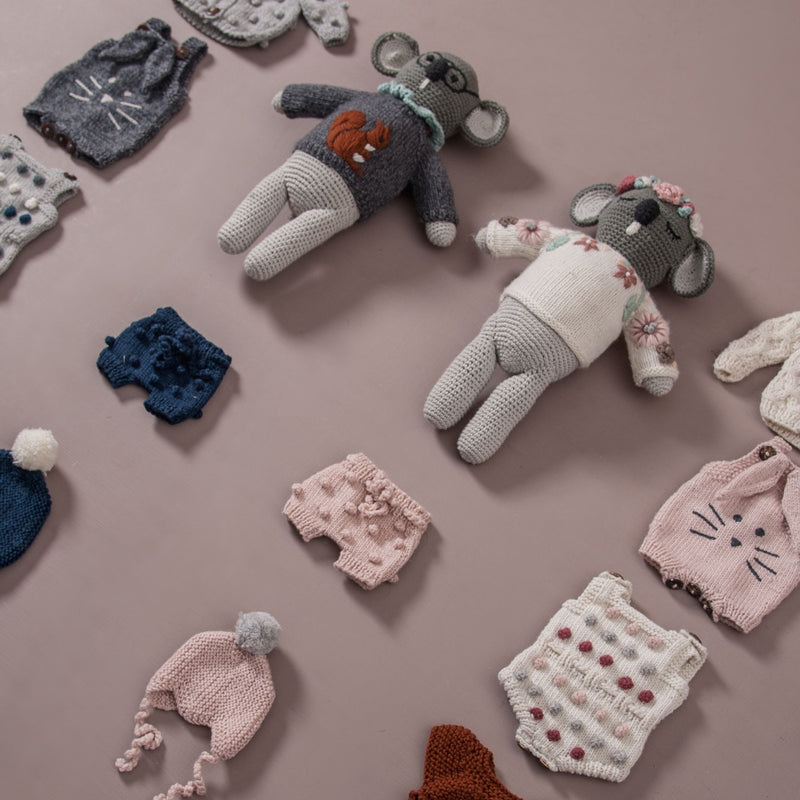 knitted doll clothes on flatlay