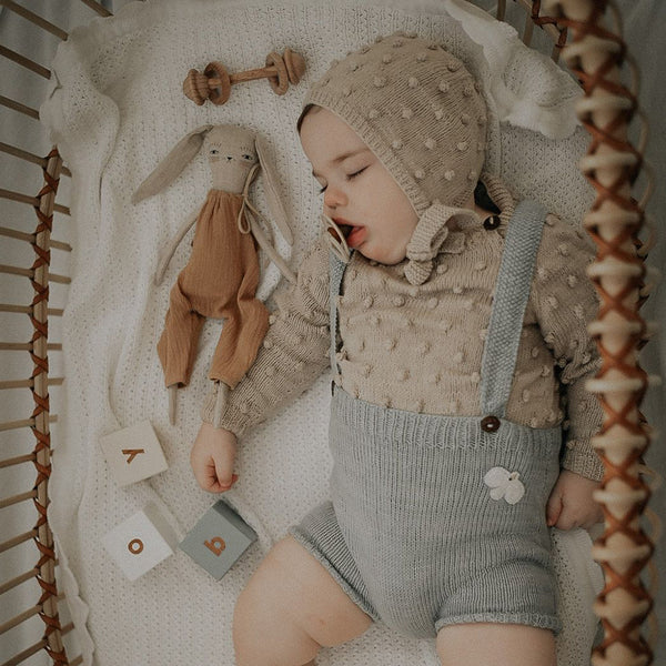 cute picture of seeping baby boy with his doll  wearing hand knitted sweater oats and bonnet in bubble style and hand knitted suspender shorts in duck blue