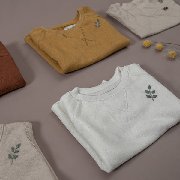 Flat lay picture of hemp/cotton sweatshirt cream white and hemp cotton sweatshirt masala along with hemp cotton t-shirts and romper