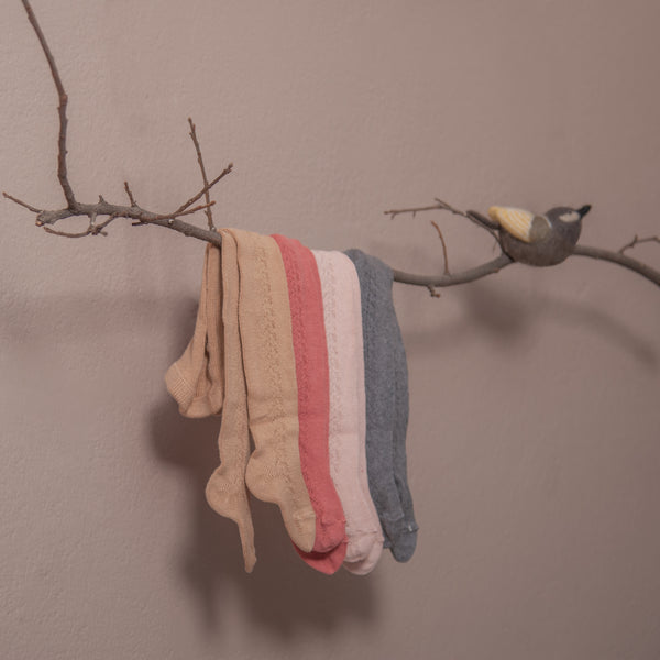 baby tights in hole pattern on side hanging on branch of tree in  four different colours : camel,pink, dusty pink and dark grey