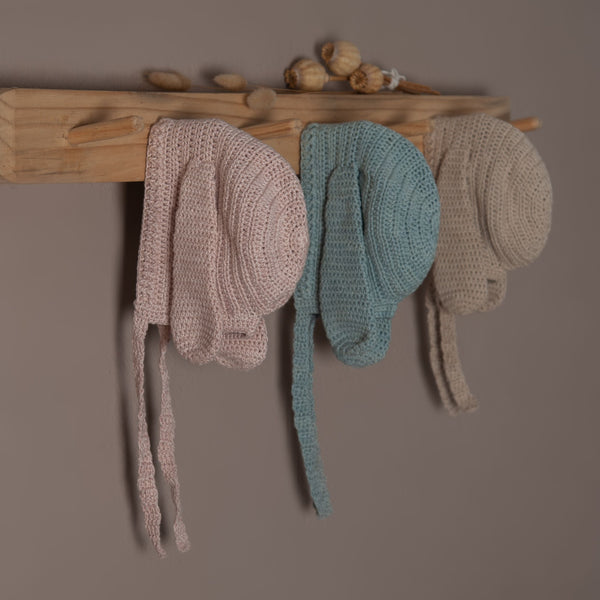 Beautiful picture of hand knitted bonnet in three different color, dusty pink,duck blue and oats with string on bunny style