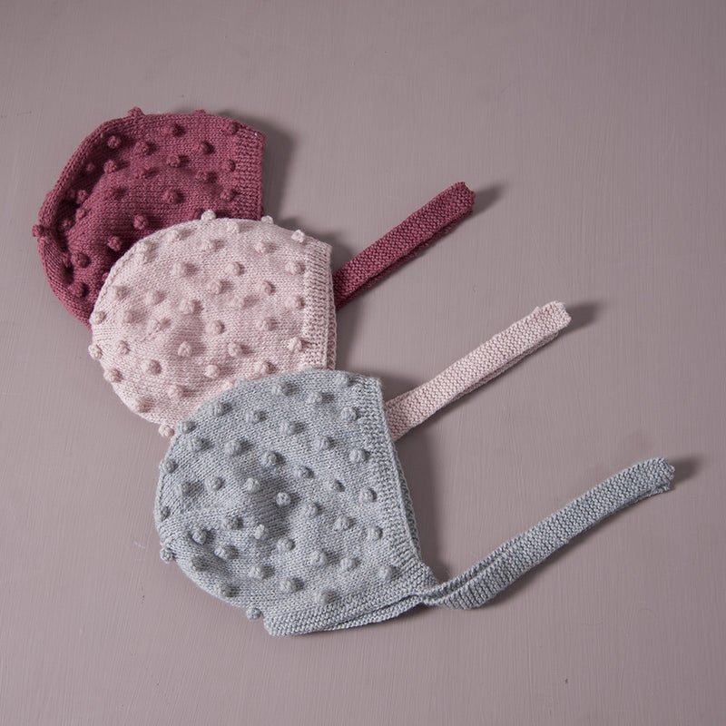 Flatlay picture of hand knitted bonnet with string ties in three different colors : deep berry, dusty pink and duck blue