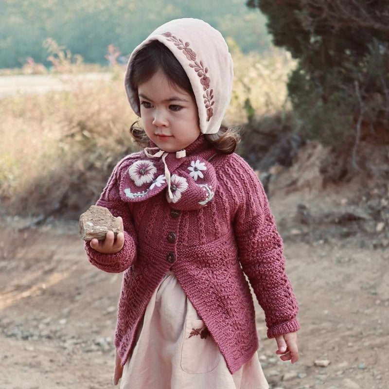 little girl wearing hand knitted scarf with floral embroidery on it, it fits perfectly with her outfit