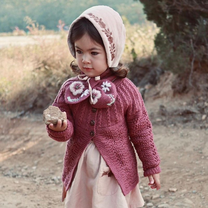 cute little girl wearing hand knitted edith cardigan in deep berry