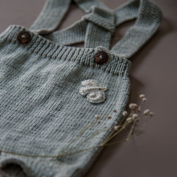 flat lay picture of hand knitted baby suspender shorts in blue with al little bird badge on left side