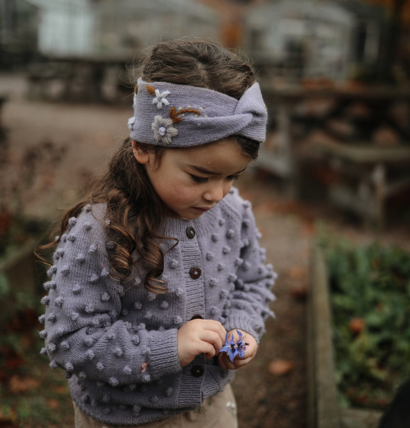little girl in hand knitted lavnder popcorn cardigan and headband with embroidered flowers