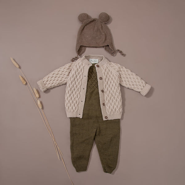 flat lay picture of hand knitted cardigan in waffle style along with hand knitted jumpsuit which has also waffle pattern in front chest part , moss in color and hand knitted bonnet with string ties and ears on it in nutty brown colour