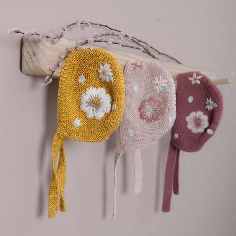 Three gorgeous bonnet are hanged in coat rack and they are knitted by hand in our signature vegan cotton, and afterwards we have embroidered this fantastic flower embroidery by hand.