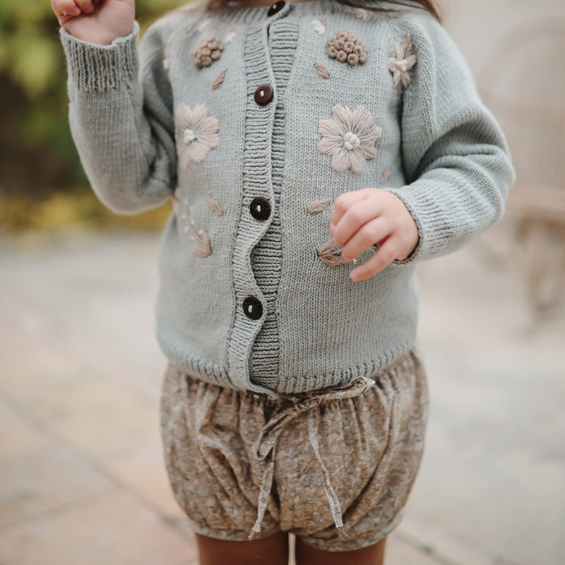 girl wearing floral embroidery cardigan in blue and bloomers with floral print on earthy color