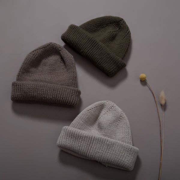 Flat lay picture of a slight oversize hat in three different colors: oats,moss and nutty brown that works so well for both mama, boys and girls.The entire hat is knitted in rib in our soft signature merino