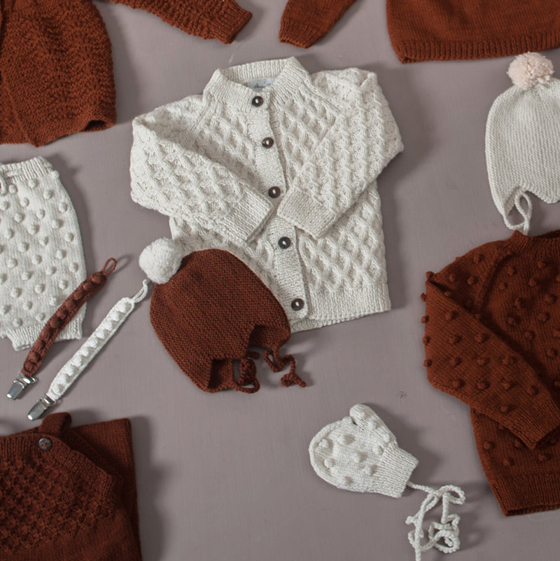 flat lay picture of cream white waffle style cardigan with different other baby outfits