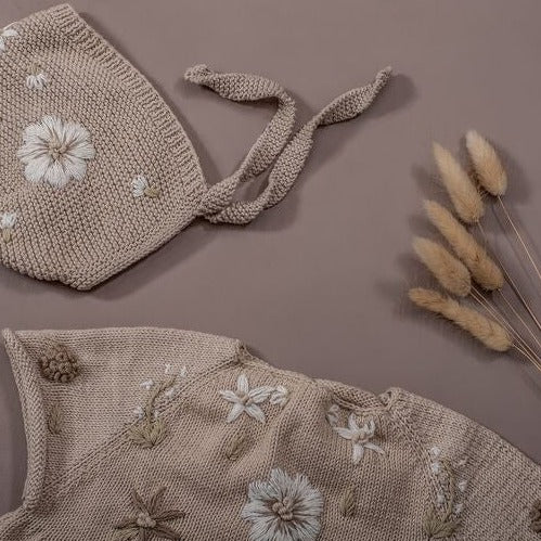 Flat lay picture of gorgeous  bonnet knitted by hand in signature vegan cotton, and afterwards with embroidered in fantastic flower embroidery by hand.