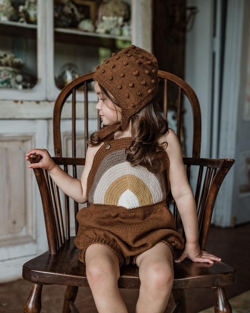 baby girl sitting in chair wearing hand knitted bonnet in bubble style, caramel in color