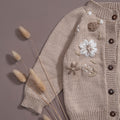 Flat lay detailed picture of hand knitted Cardigan with beautifully embroidered floral designs on it, those little detailed embroidery makes the cardigan perfect.