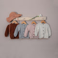 four different hand knitted cardigan in four different color hanged in coat rack along with hat