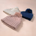 flat lay picture of hand knitted waffle pattern hat in dusty pink,cream white and navy