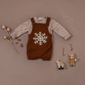 flat lay picture of hand knitted romper with snowflake embroidery on it