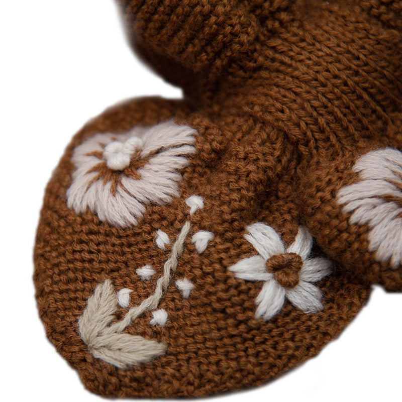 Detail picture of hand knitted scarf with floral embroidery on it