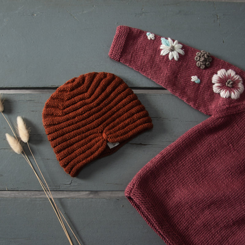 hand knitted hat in our dreamy soft merino wool with hand knitted sweater which has floral embroidery on it