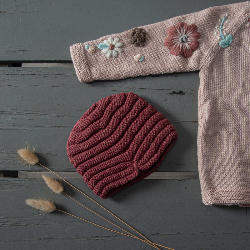 hand knitted hat in our dreamy soft merino wool along with hand knitted sweater with floral embroidery on it